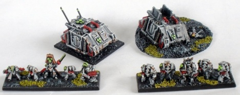 Sin Eater Command Squad and Rhino transport plus Sin Eater Terminator Squad with Terminator Chaplain. The wrecked Rhino on the right is an objective marker